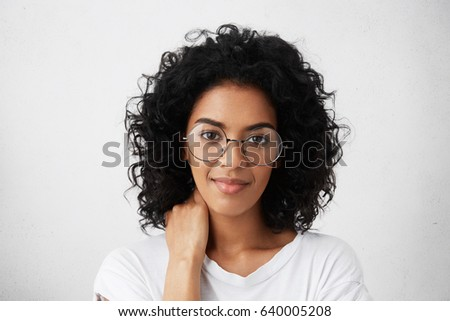 Portrait of beautiful dark-skinned young woman with curly brunette hair looking at camera with cute shy smile, rubbing her neck, feeling a bit shy or uncomfortable. Human feelings and emotions