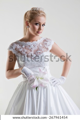 Portrait of beautiful delicate blonde bride in wedding dress with flowers and lilies in her hand, on white background in Studio - stock photo