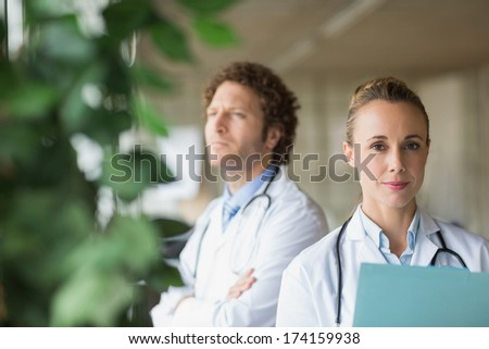 Portrait of beautiful doctor with colleague in background at hospital - stock photo