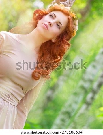 Portrait of beautiful dreamy woman in the park, gentle flower wreath in curly red hair, sensual elegant female enjoying spring nature - stock photo