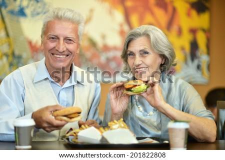 Portrait of beautiful elderly couple eating fast food - stock photo