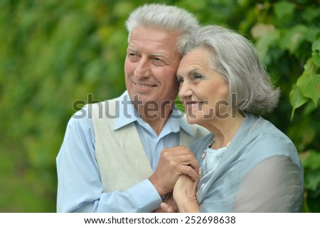 Portrait of beautiful elderly couple outdoor in summer park - stock photo