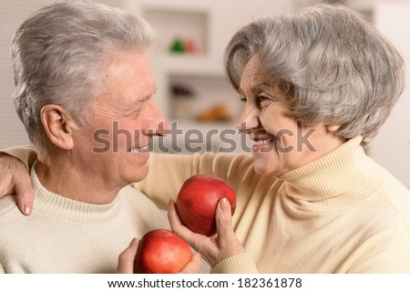 Portrait of beautiful elderly couple with apples