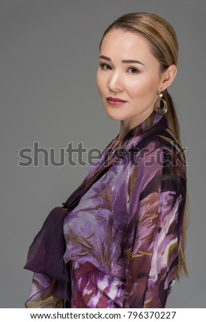 portrait of beautiful elegant kazakh woman looking at camera isolated on grey