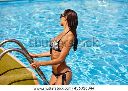 Portrait of beautiful elegant tanned woman relaxing in bikini and sunglasses in swimming pool spa. Hot summer day and bright sunny light. - stock photo