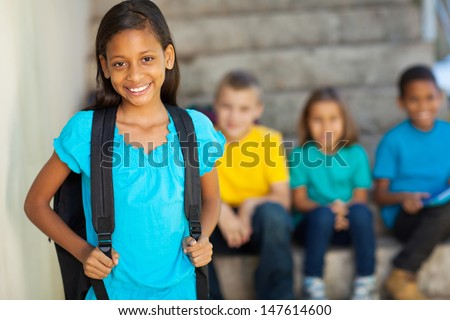 portrait of beautiful elementary school girl with schoolmates on background - stock photo