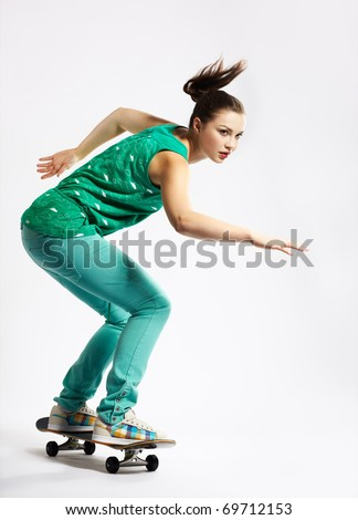 portrait of beautiful extreme girl with skateboard on gray