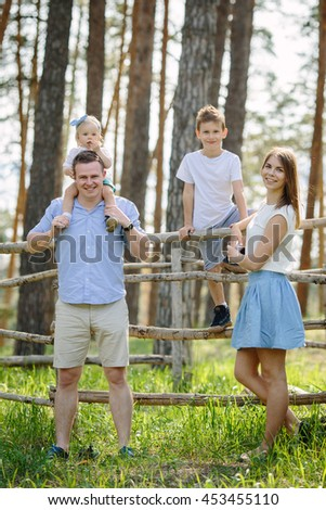 Portrait of beautiful family of four people mother father son daughter park near forest - stock photo