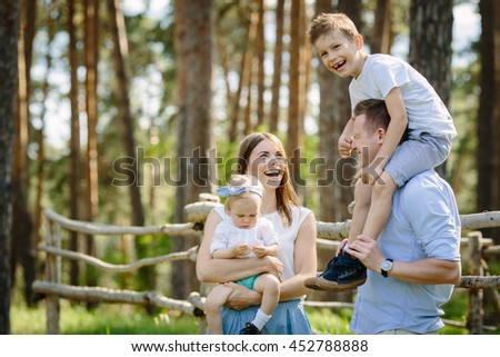 Portrait of beautiful family of four people mother father son daughter talking park near forest - stock photo