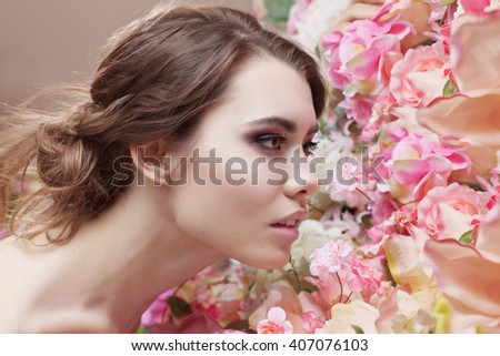 Portrait of  beautiful fashion girl, smelling a many flowers. Beautiful makeup and messy romantic hairstyle. Flowers background. Green eyes.