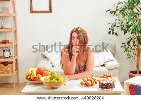 Portrait of beautiful fat woman sitting at table full of different foods: unhealthy and healthy ones at home. - stock photo