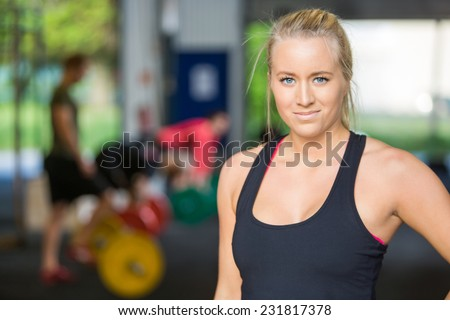 Portrait of beautiful female athlete standing in Cross-Fitess Center - stock photo