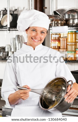 Portrait of beautiful female chef mixing egg with wire whisk in bowl at commercial kitchen - stock photo