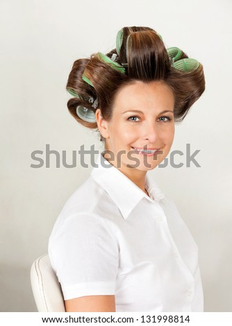 Portrait of beautiful female client with hair curlers in salon - stock photo