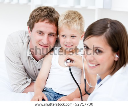 Portrait of beautiful female doctor examining a little boy with his father at the hospital