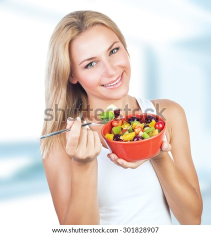 Portrait of beautiful female eating tasty fruit salad for breakfast at home, healthy lifestyle, body care, organic nutrition and dieting concept