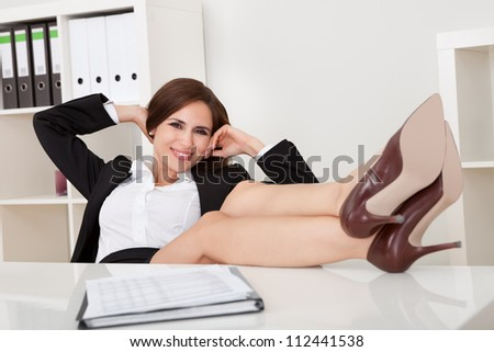 Portrait of beautiful female executive relaxing with feet on desk at office - stock photo
