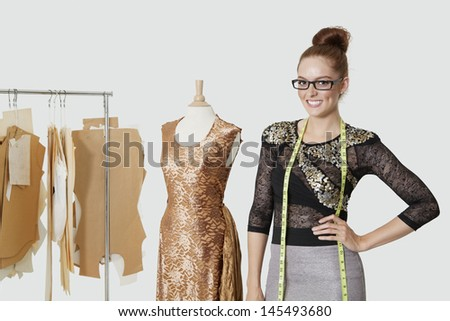 Portrait of beautiful female fashion designer standing with hand on hip over gray background - stock photo