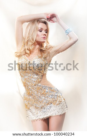 portrait of beautiful female fashion model posing against gold fabric