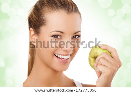 portrait of beautiful female holding green apple and smiling, showing her beautiful white teeth.Studio shot, isolation on white. - stock photo