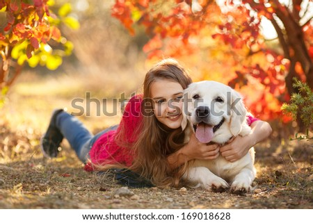 portrait of Beautiful female lying down on the ground with her labrador retriever dog in a park