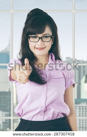Portrait of beautiful female manager looks satisfied and showing thumb up in the office - stock photo
