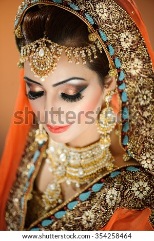 Portrait of beautiful female model in a bridal setting in indian traditional costume and ethnic jewellery - stock photo