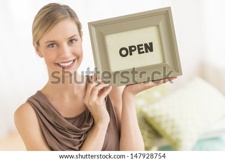 "Portrait of beautiful female owner holding framed ""open"" sign in bedding store - stock photo"