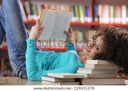 Portrait of beautiful female student in library reading a book - stock photo