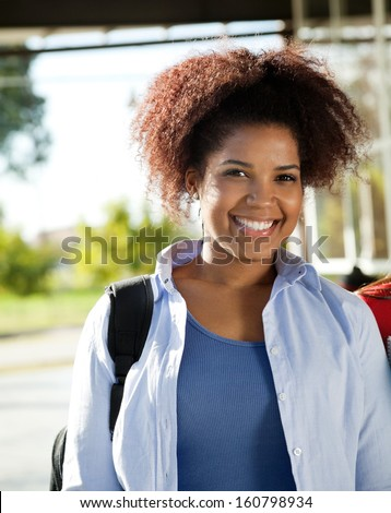 Portrait of beautiful female student smiling on college campus