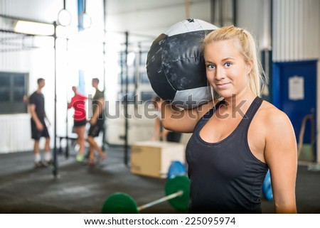 Portrait of beautiful fit woman carrying medicine ball at crossfit gym - stock photo