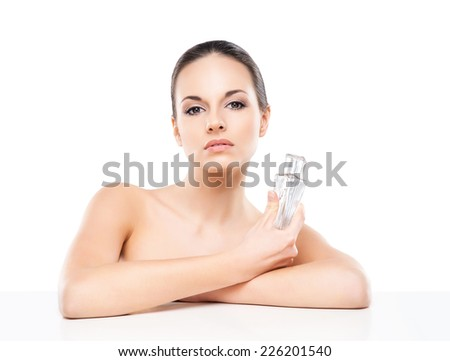 Portrait of beautiful, fresh, healthy and sensual woman with a bottle of perfume essence isolated on white - stock photo
