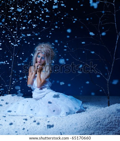 portrait of beautiful frozen fairy nymph girl sitting in snowfall - stock photo