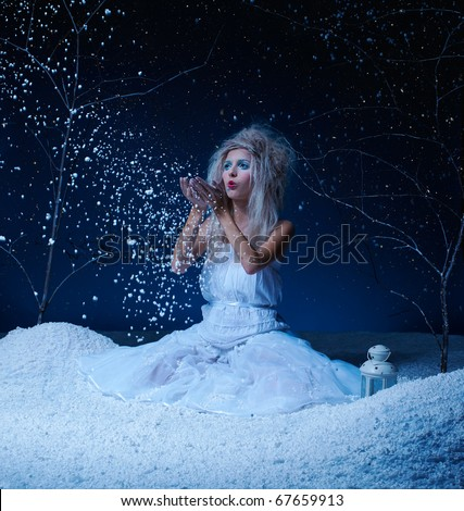 portrait of beautiful frozen fairy nymph girl sitting on snow and blowing snowflakes from her hands
