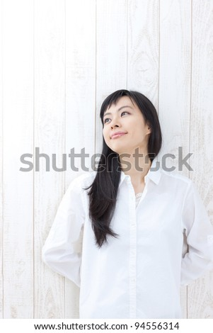 portrait of beautiful girl against a rustic wooden wall - stock photo