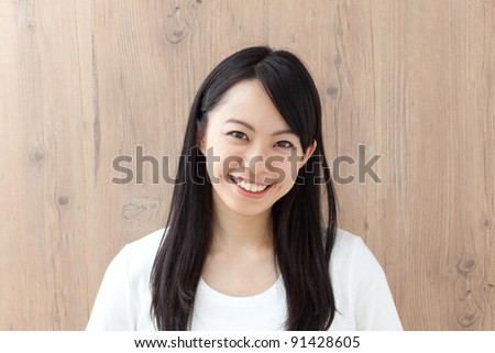 portrait of beautiful girl against a wooden wall - stock photo