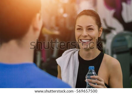 Portrait of beautiful girl at gym, talking with personal trainer and drinking water on break