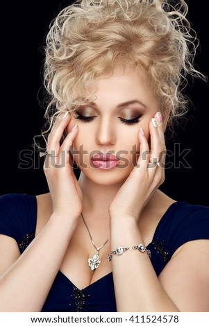 Portrait of beautiful girl blonde with gold evening makeup, full lips, French manicure, neat nails. Brilliant jewelry, silver pendant, ring, bracelet. Black Studio background. - stock photo