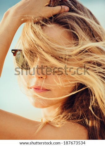 Portrait of beautiful girl close-up, wind fluttering her hair. Beach fashion lifestyle.
