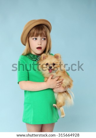 Portrait of beautiful girl, cute little dog on the hands. Blue background. Studio shot - stock photo