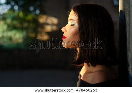 Portrait of beautiful girl enjoying sunlight in abandoned building.