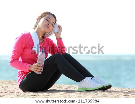 Portrait of beautiful girl having a break on the beach after doing some exercise - stock photo