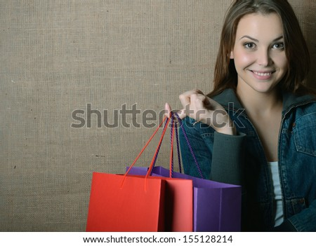 Portrait of beautiful girl holding colored shopping bags, toned