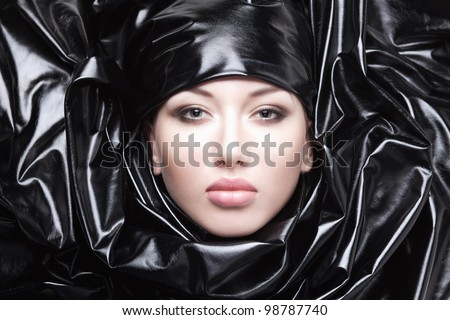 Portrait of beautiful girl in black fabric. Looking to camera.