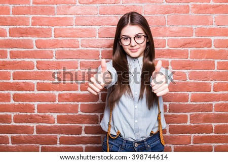 Portrait of beautiful girl in casual clothes showing OK sign, looking in camera and smiling while standing against red brick wall - stock photo