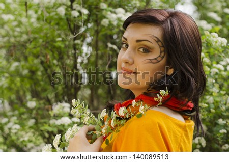 Portrait of beautiful girl in flowers with picture on face