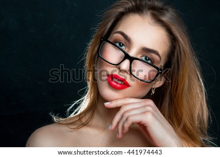 portrait of beautiful girl in glasses and with red lips looking at the camera in studio