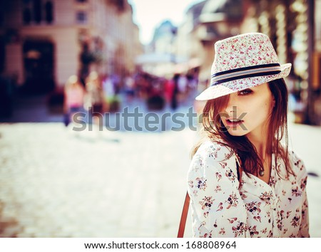Portrait of beautiful girl in hat outdoors - stock photo