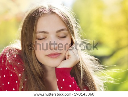 Portrait of beautiful girl in red cardigan daydreaming in green prak - stock photo