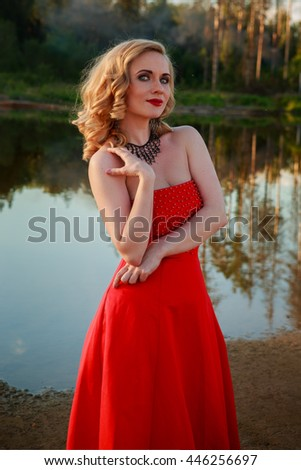 Portrait of beautiful girl in red dress in nature
